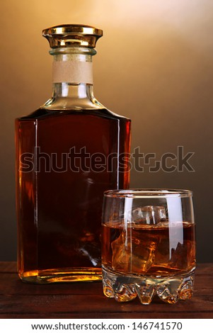 Brandy with ice on wooden table on brown background - stock photo