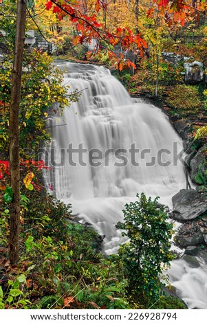 Brandywine Falls, a waterfall in Ohio's Cuyahoga Valley National Park, cascades down a cliff surrounded by vivid fall foliage. - stock photo