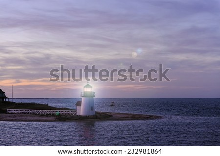 Brant Point Lighthouse during the blue hour just after sunset. Brant Point light house, at the entrance to Nantucket Harbor, Cape Cod, Massachusetts, is the shortest lighthouse in New England. - stock photo