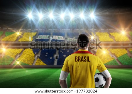 Brasil football player holding ball against stadium full of brasil football fans - stock photo