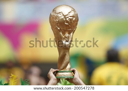 BRASILIA, BRAZIL - JUNE 23, 2014: A fan showing a fake World Cup Trophy during the World Cup Group A game between Cameroon and Brazil in the National Stadium. NO USE IN BRAZIL. - stock photo