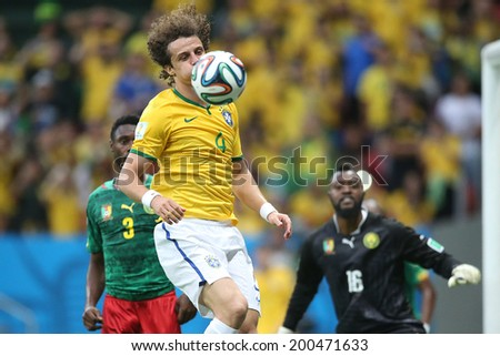 BRASILIA, BRAZIL - June 23, 2014: Oscar of Brazil and Nguemo of Cameroon compete for the ball during the game between Brazil and Cameroon at Estadio Nacional Mane Garrincha. No Use in Brazil.