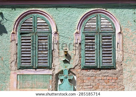 Brasov, Romania - June 9, 2013: Green old house windows with wood curtains from Brasov, Romania