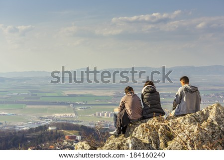 BRASOV, ROMANIA - MARCH 23: Three unidentified young hikers sit on Tampa Mountain cliff and enjoy the panorama on March 23, 2014 in Brasov, one of the most visited cities in Romania.