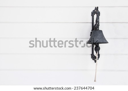 Brass bell on white wood wall. - stock photo