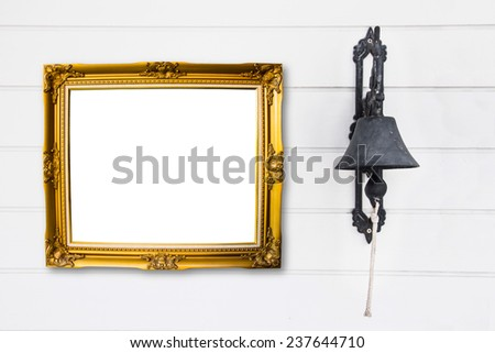 Brass bell with vintage frame on white wood wall. - stock photo