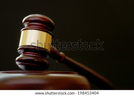 Brass bound wooden gavel resting in the upright position on a plinth, low angle view on a dark background with copyspace conceptual of justice, a judge or auctioneer - stock photo