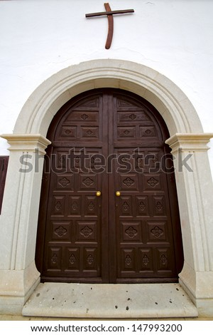 brass brown knocker in a brown closed wood  church door and white wall lanzarote abstract  spain canarias  - stock photo