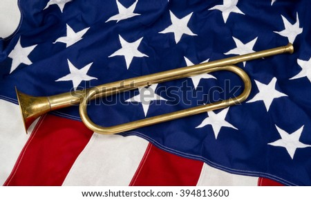 Brass bugle on a American flag. - stock photo