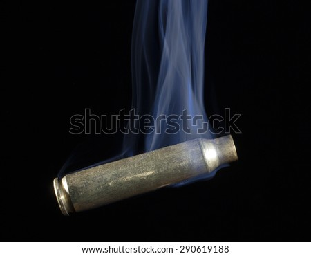 Brass casing that has been shot with smoke on a black background - stock photo