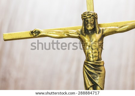 Brass  Cross with crucified Jesus Christ on wooden bur background, close up