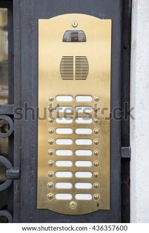 Brass intercom on a metal door - stock photo