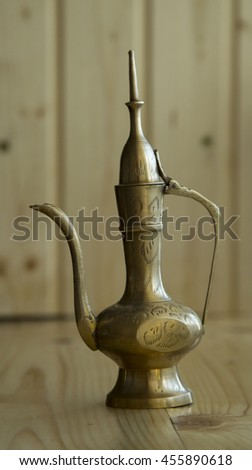 brass kettle on wood background - stock photo