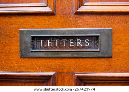 Brass letterbox and wooden door - stock photo