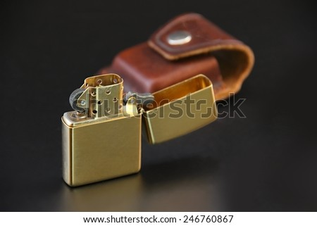 Brass lighter and leather sheath on black background.