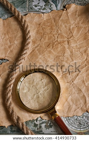 Brass magnifying glass lies on an old paper or parchment