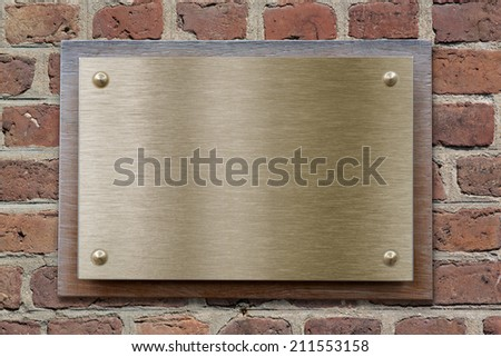 Brass or bronze metal plate on brick wall - stock photo