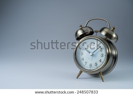 Brass Retro Alarm Clock on Grey background with copy space