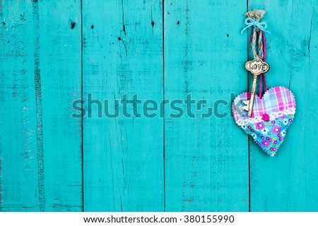 Brass skeleton key with LOVE and pink and turquoise country fabric heart hanging on antique rustic teal blue wood background; security and love concept - stock photo
