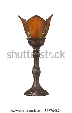 Brass victorian styled lamp with orange glass on a white background