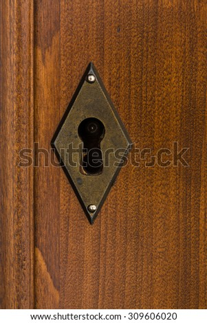 brass vintage keyhole in cherry wood - stock photo