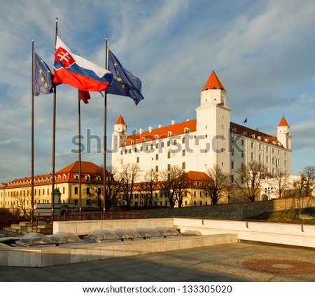 Bratislava castle with slovak flag and flag of European Union in the foreground - stock photo