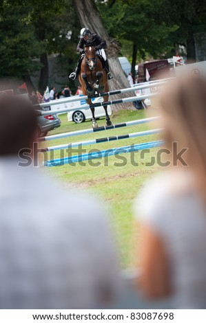 BRATISLAVA, SLOVAKIA - AUGUST 13: spectators watch as Andy Candin on horse Carlo 281 jumps over hurdle at Grand Prix Bratislava on August 13, 2011 in Bratislava, Slovakia - stock photo
