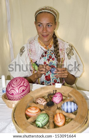 BRATISLAVA, SLOVAKIA - AUGUST 31, 2013 - The young woman in traditional outfit is decorating the easter eggs during Festival Craftsmen Days  August 31th 2013 in Bratislava.