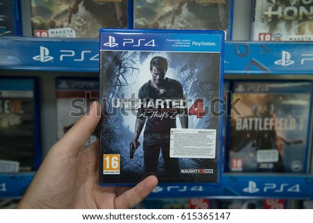 Bratislava, Slovakia, circa april 2017: Man holding Uncharted 4 A thief's end videogame on Sony Playstation 4 console in store
