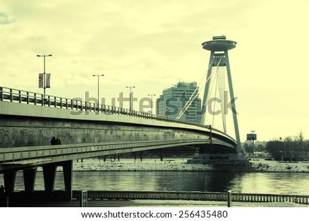 BRATISLAVA, SLOVAKIA - FEBRUARY 3, 2015: The Novy Most Bridge across the Danube River in Bratislava, Slovakia. Toned image  - stock photo
