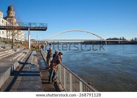 BRATISLAVA, SLOVAKIA - JANUARY 6, 2015: People on the shore of Danube river with Apollo bridge in the background. - stock photo