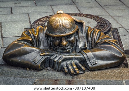 BRATISLAVA, SLOVAKIA - MAY 5. Cumil (The Watcher) or Man at work - statue of man peeking out from under a manhole cover in Bratislava, Slovakia. Popular attraction was made in 1997 by Viktor Hulik.