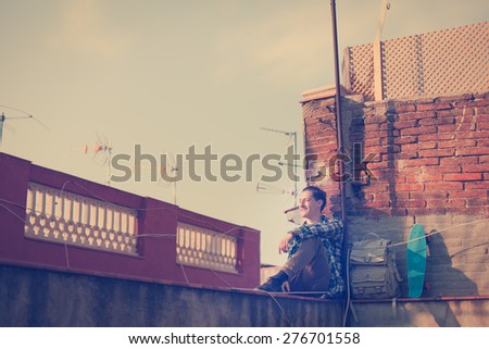 Brave and smiling traveler man sitting on the edge on high roof and watching far away, with backpack and skateboard (intentional vintage color) - stock photo