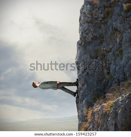 Brave businessman walks vertically over the mountain