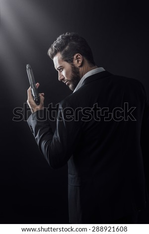 Brave cool man holding a gun on dark background - stock photo