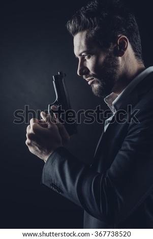 Brave cool man holding a gun on dark background - stock photo