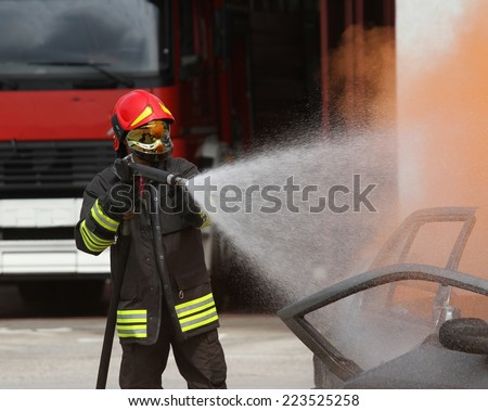 brave firefighter with helmet off the car burned with the foam