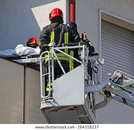 brave firefighters on the cage save the wounded person with the stretcher