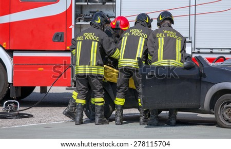 brave Firefighters pull in wounded by car plates after highway crash - stock photo