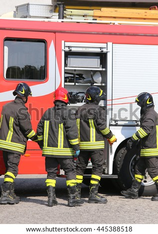 brave firefighters with fire engine truck during an exercise in fire brigade station