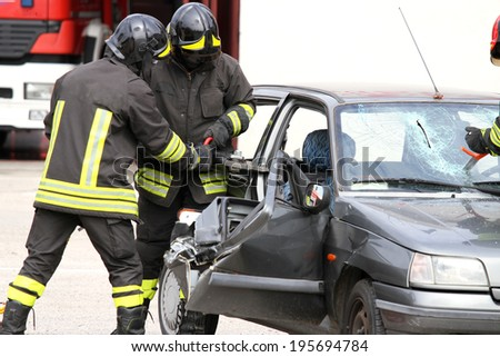 brave firefighters with pneumatic shears open the car doors