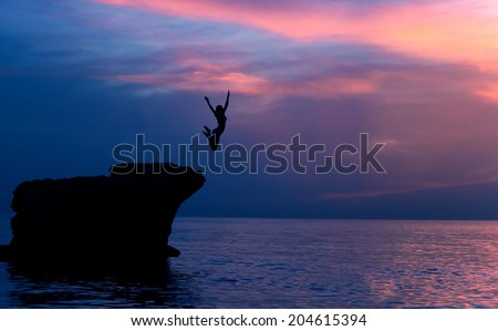 Brave girl jumping from the rocks in the evening on beautiful purple sunset background, summer adventure, freedom concept - stock photo