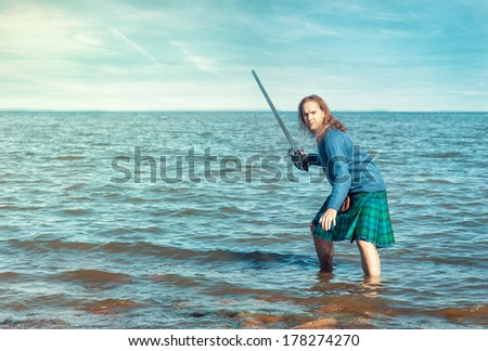 Brave man with sword in scottish costume  - stock photo