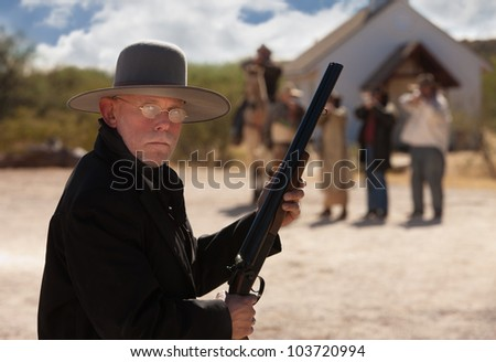 Brave old west cowboy under attack from outlaws - stock photo