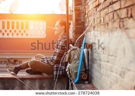 Brave smiling traveler man sitting on the edge of the roof and listening music in earphones with backpack and skateboard (intentional sun glare) - stock photo