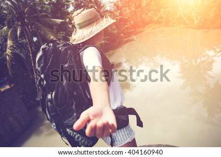Brave traveling woman with backpack walking ahead near big tropical river (intentional sun glare and vintage color) - stock photo