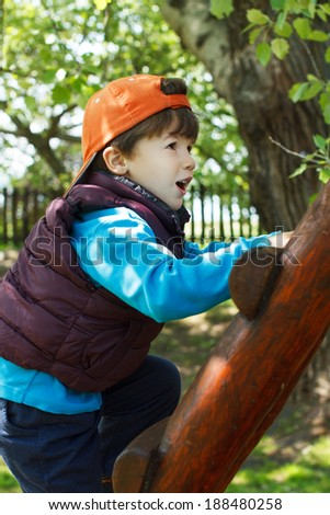 Brave young boy in cap climb up on ladder - stock photo
