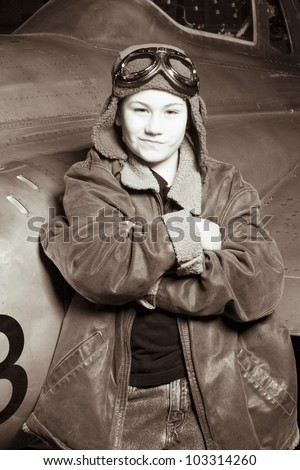 Brave young pilot resting against airplane, smirking at camera - stock photo
