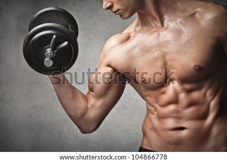 Brawny bare-chested young man lifting weights - stock photo