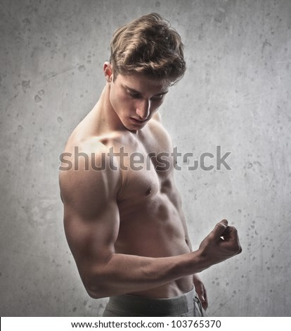 Brawny bare-chested young man showing his biceps - stock photo